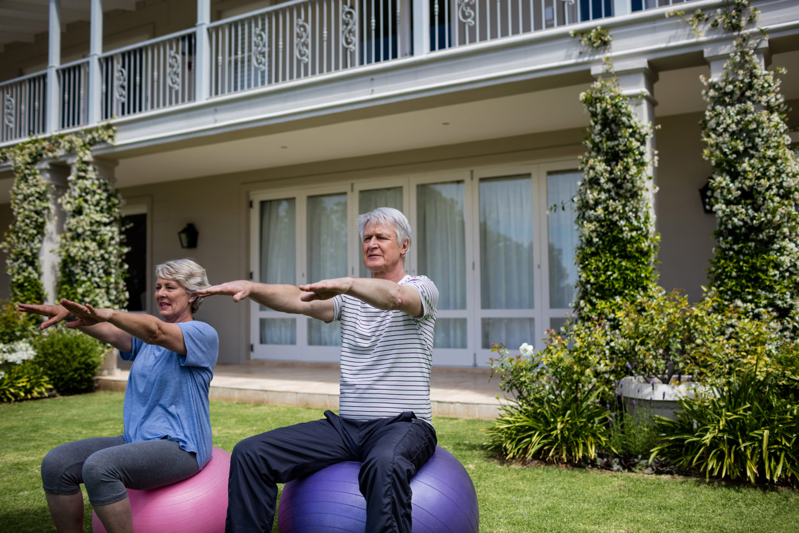 Senior couple exercising on fitness ball in lawn