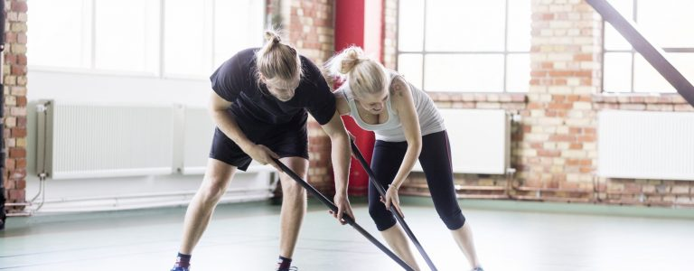 Full length of man and woman playing hockey in health club