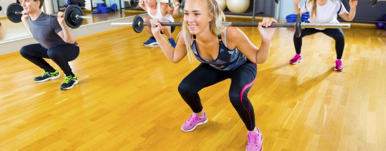 Full length of young male and female friends lifting barbell rods in gym